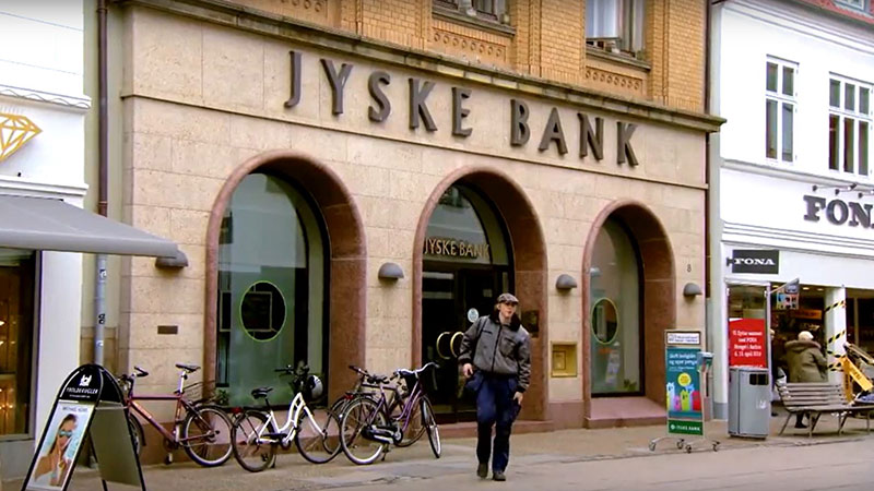 Person walks out of JYSKE Bank onto a road lined with bicycles, a bench, and store signs.